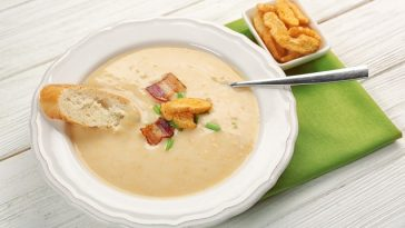 Delicious beer cheese soup with croutons and fried bacon on table